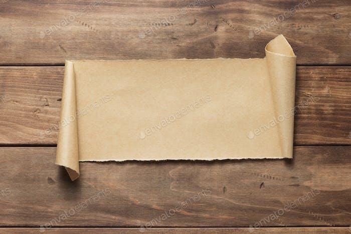 изогнутая или прокручиватая бумага на деревянном фоне