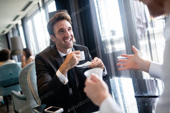 Coffee break. Two cheerful business men talking in a restaurant