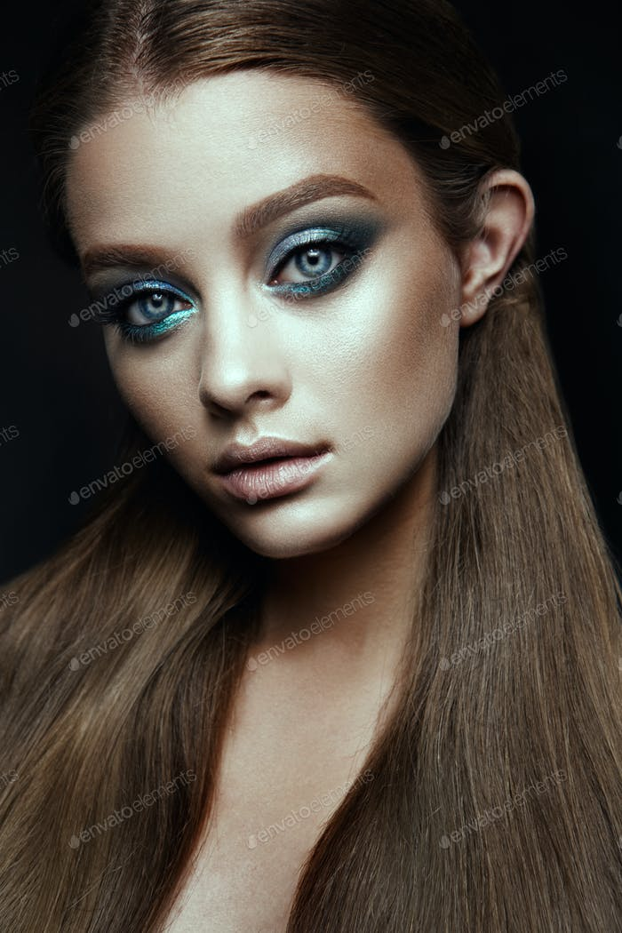 Fashion model Woman with fantasy make up. Long blowing brown hair.