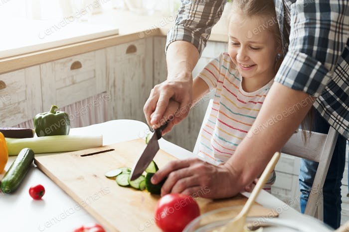 Little girl and dad having fun while cooking in kitchen