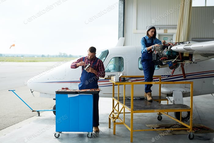 Engineers repairing airplane