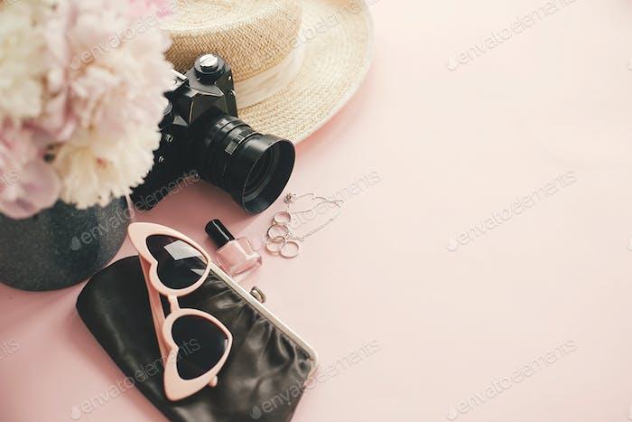 Stylish photo camera, sunglasses, jewelry,straw hat, bag, cosmetics  on pink paper