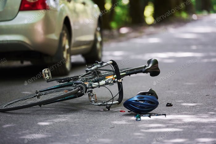 The place of the break. Bicycle and silver colored car accident on the road at forest at daytime