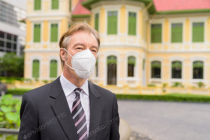 Face of mature businessman with mask for protection from corona virus outbreak thinking in the city