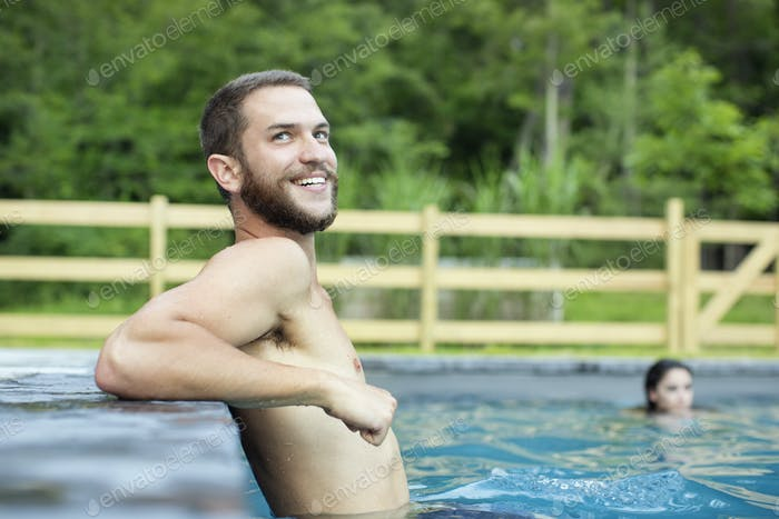 A man and woman swimming in a lake or pool.