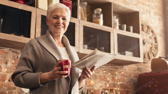Fröhlich Alter Frau stehend in der Küche mit Morgenkaffee und Zeitung