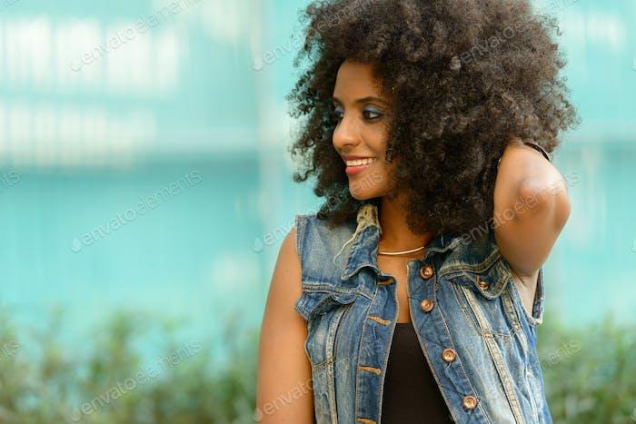 Joven hermosa mujer africana con cabello afro en la ciudad