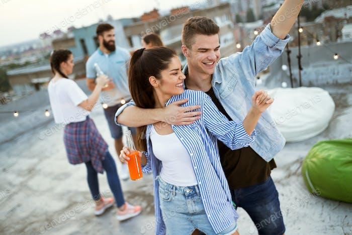 Happy couple enjoying drinks and balcony party