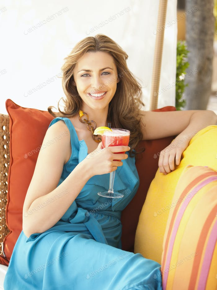 Красивая хорошо одетая женщина пьет коктейль в открытом лаундже на роскошном курорте