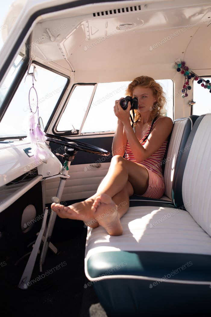 Front view of beautiful Caucasian woman taking photo with digital camera in camper van at beach