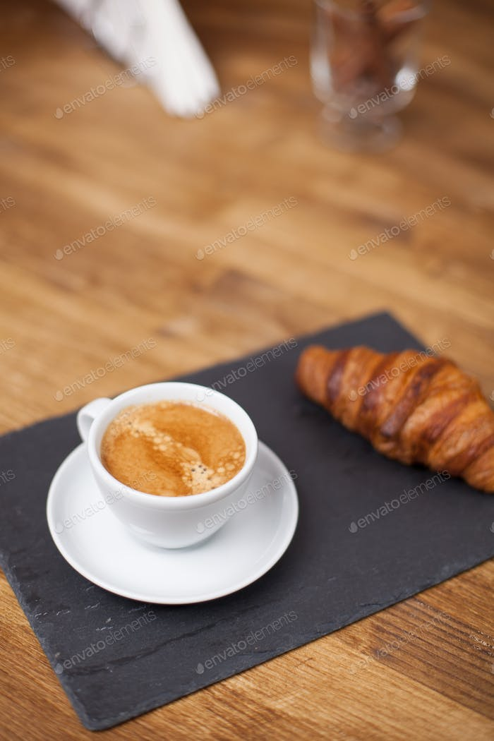 Breakfast with espresso cup of hot coffee and croissant on a black stone plate