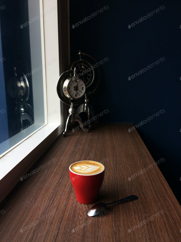 Red cup of cappuccino coffee in the morning time with vintage clock background