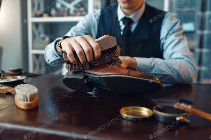 Shoemaker wipes black shoe polish, footwear repair