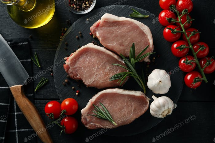 Composition with raw meat for steak and ingredients on wooden background