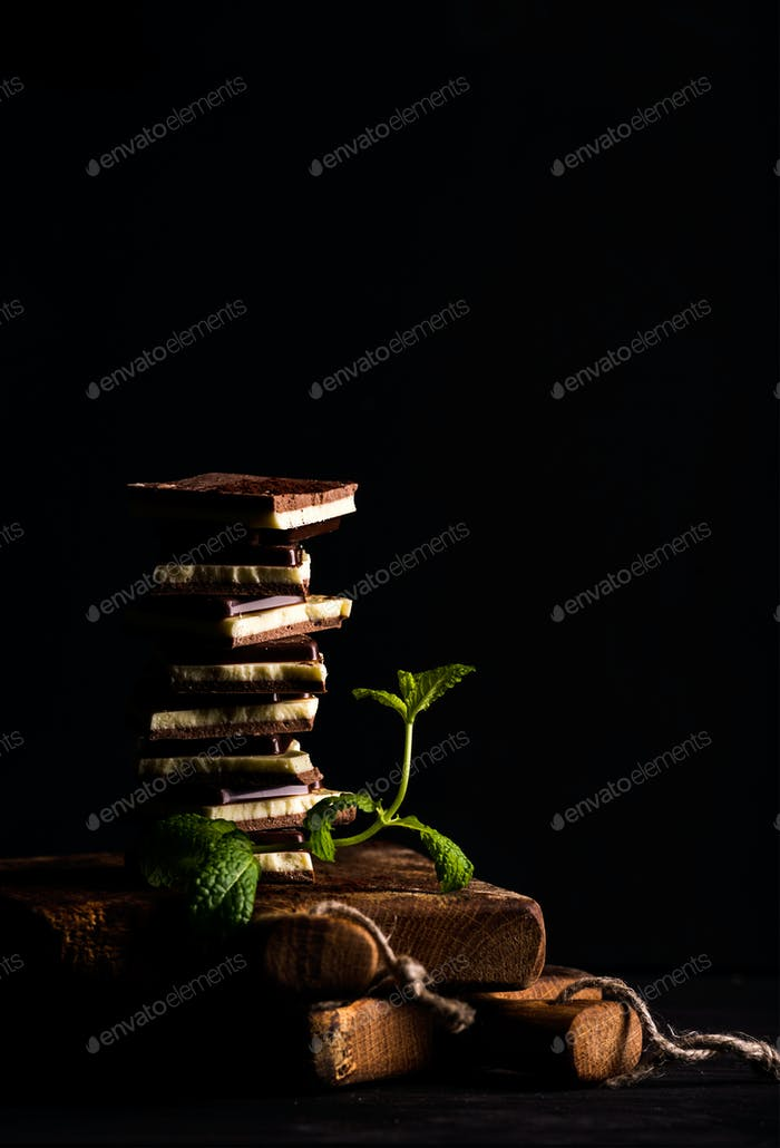 Triple layered chocolate pieces stack or tower with branch of fresh mint on black background