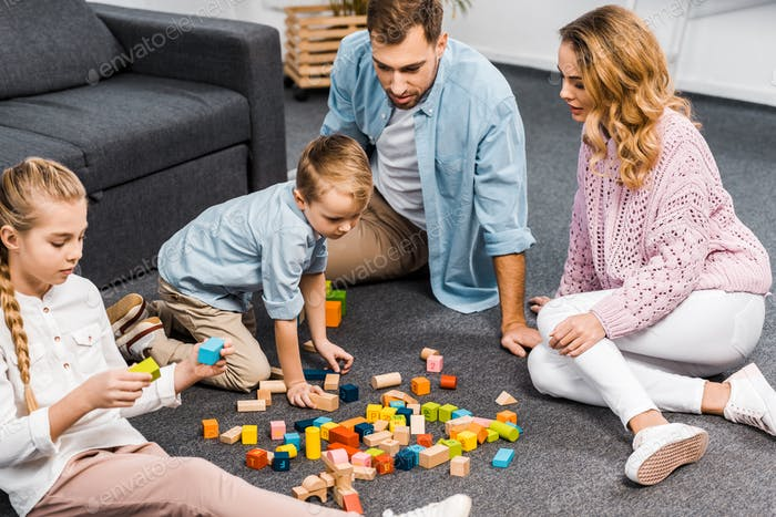 parents and siblings playing with wooden blocks on floor in living room