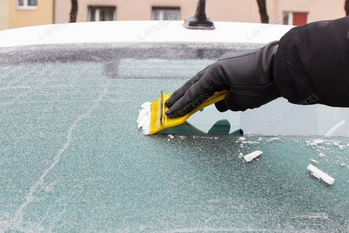 Hand holding scraper and removing ice or snow from car window