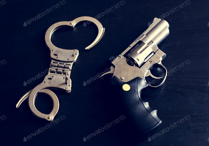 Handcuffs and gun with black background