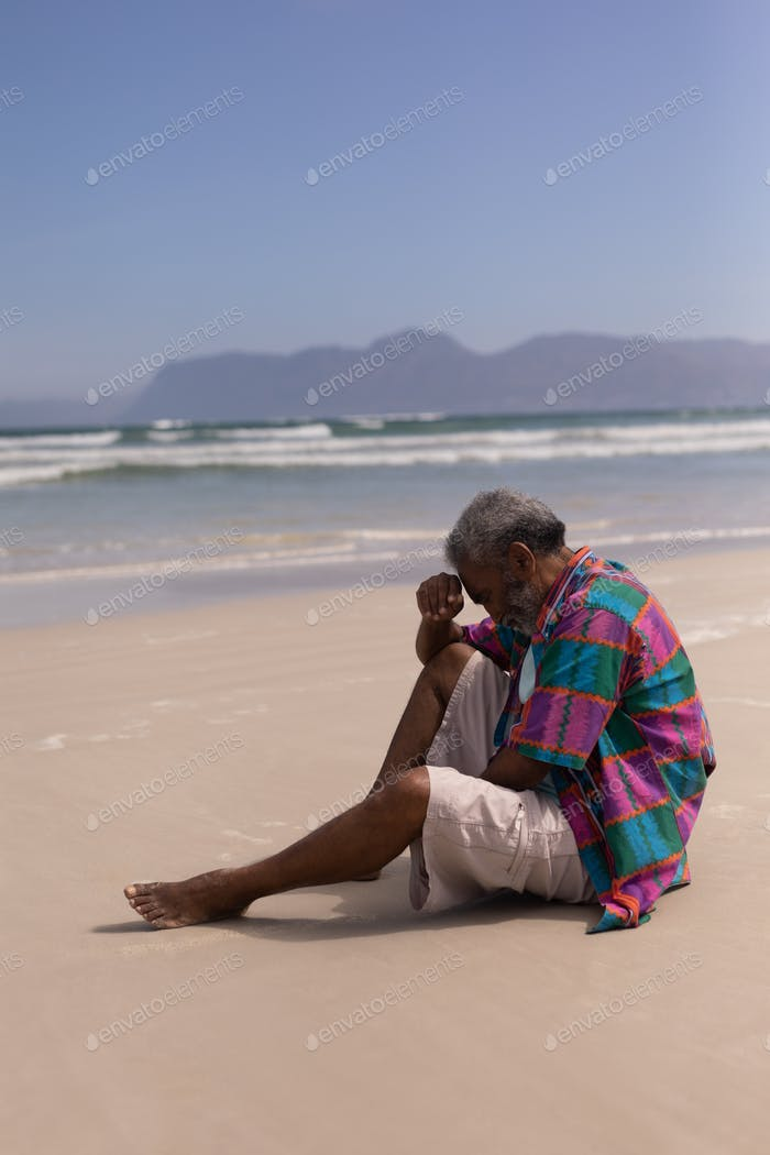 Side view of sad senior man with hand on forehead sitting on beach in the sunshine