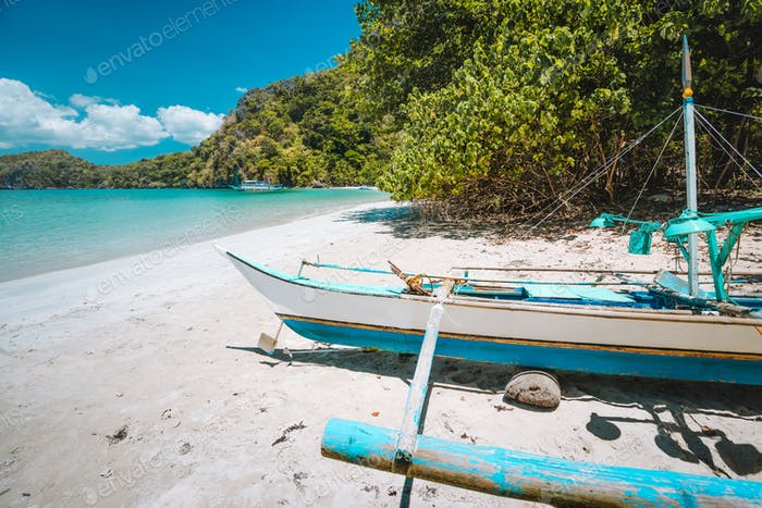 Traditional banca fishermen boat on sandy remote tropical beach. El Nido, Philippines