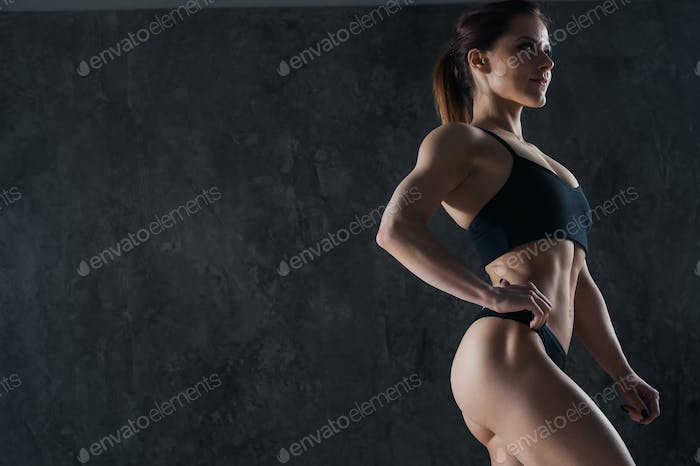 Close-up of a perfect female body over dark studio background