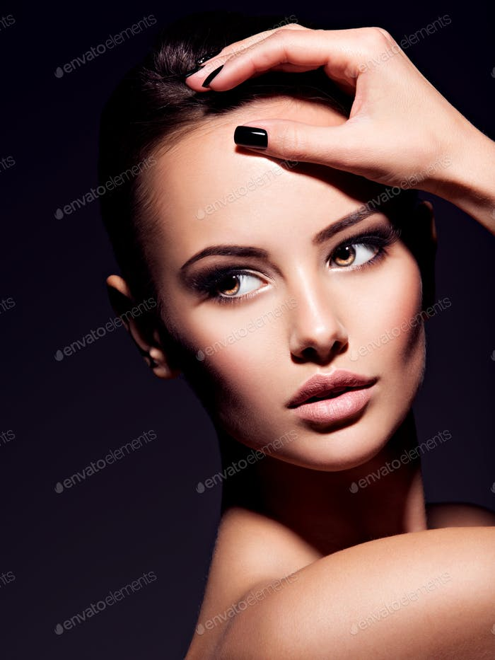 Close-up face of a beautiful sexy woman with brown make-up of  e