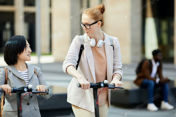 Girls Riding Scooters in City