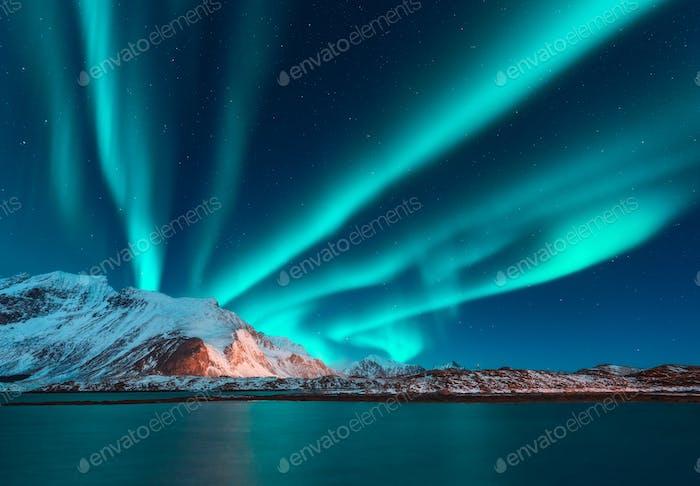Aurora borealis above the snow covered mountain