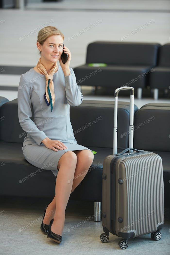 Elegant Businesswoman Speaking by Phone in Waiting Lounge