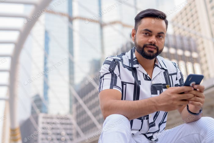 Young bearded Indian man with phone sitting in the city outdoors
