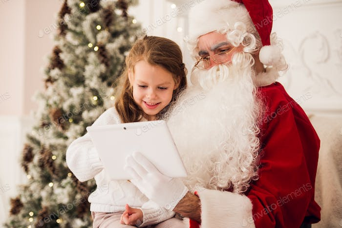 Little girl sitting with Santa using tablet on the armchair at home living room