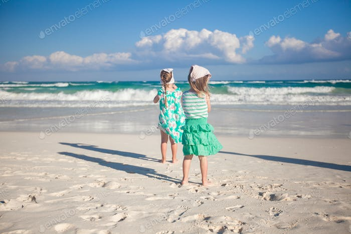 Two little sisters running at tropical beach in Mexico on sunny day