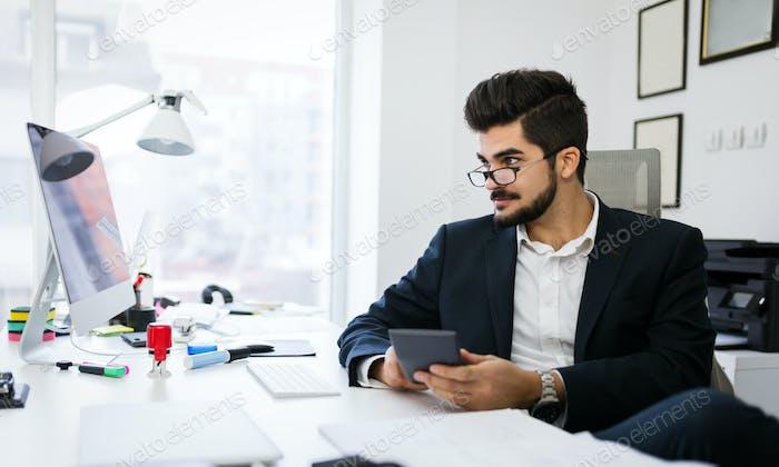 Bild von beschäftigten Mann mit Taschenrechner im Büro