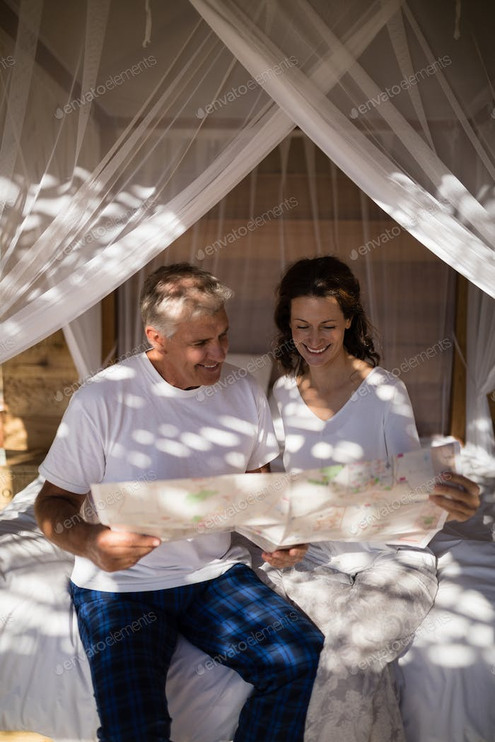 Happy couple looking at map while relaxing on canopy bed