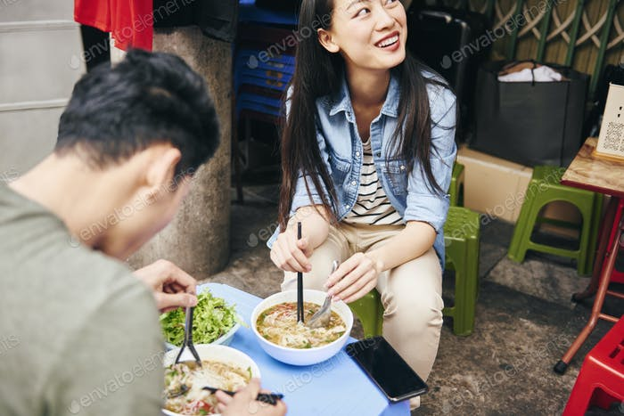 Close up of couple eating pho soup in the city