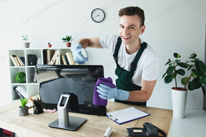 handsome young cleaner in rubber gloves cleaning computer monitor and smiling at camera