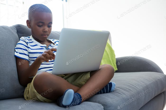 Boy using laptop while sitting with crossed legged on sofa at home