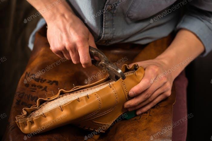 Shoemaker sitting in workshop making shoes