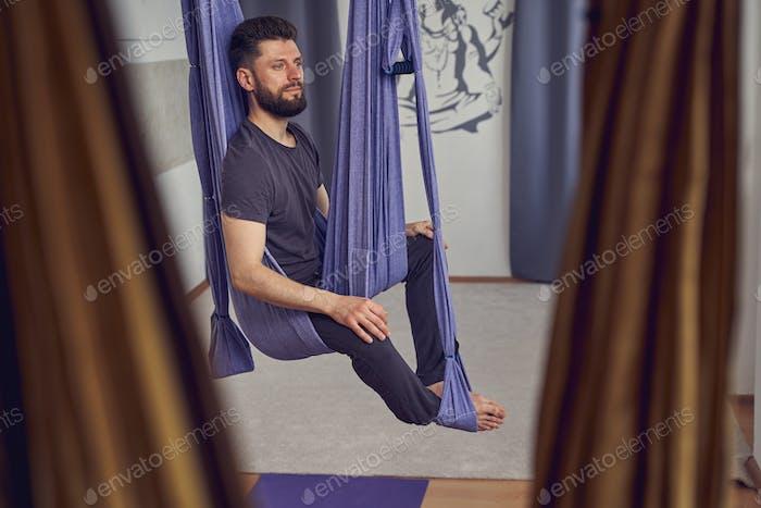 Joven barbudo practicando yoga antigravedad en estudio