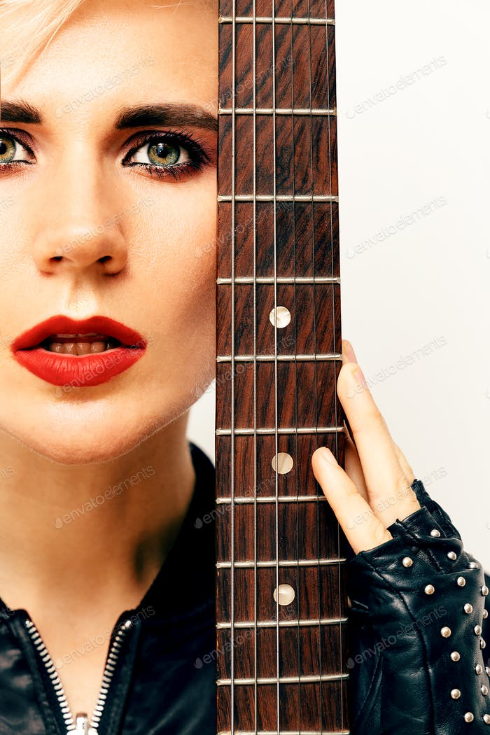 Portrait of sensual Model with electro guitar. Rock style