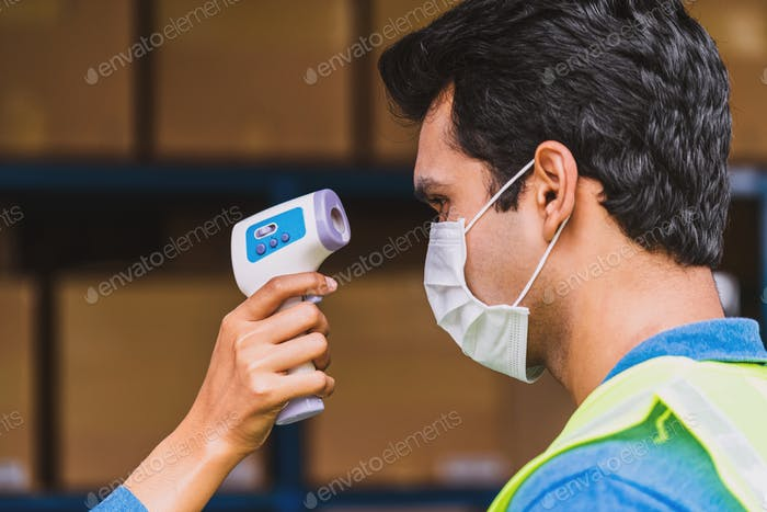 Closeup hand of Muslim woman worker using Medical Digital Infrared Thermometer