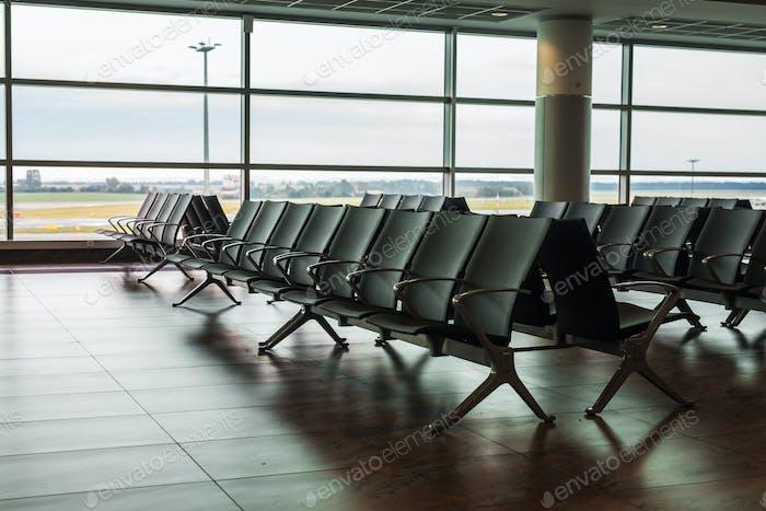 Zona de espera de la terminal del aeropuerto vacía con sillas.