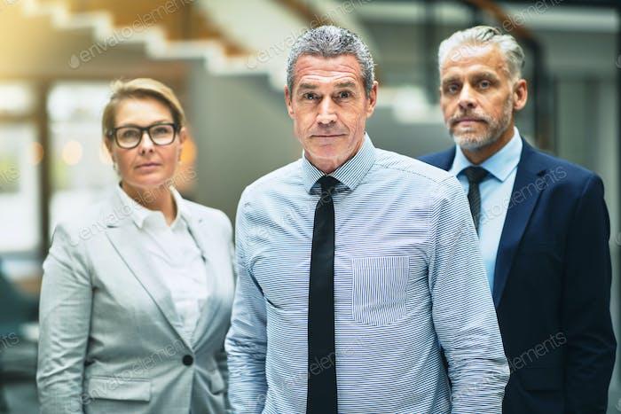 Уверенный зрелый бизнесмен, стоящий с коллегами в офисе