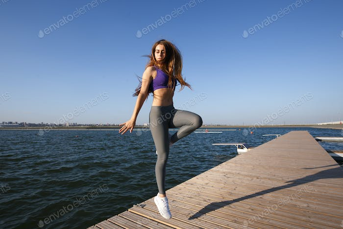 Girl dressed in sports clothes jumping on the wooden pier on a summer day