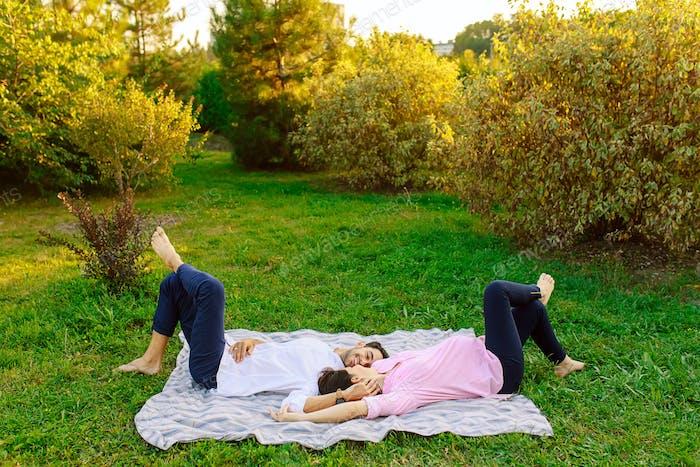 Junges Paar auf Gras liegend und lächelnd und berühren sanft einander