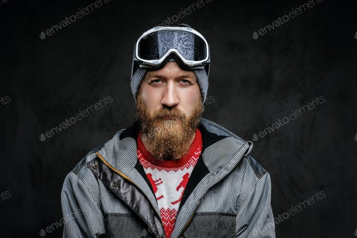 Confident man with a red beard wearing a full equipment for extreme snowboarding