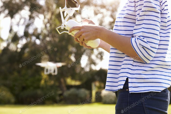 Close Up Of Woman Flying Drone Quadcopter In Garden