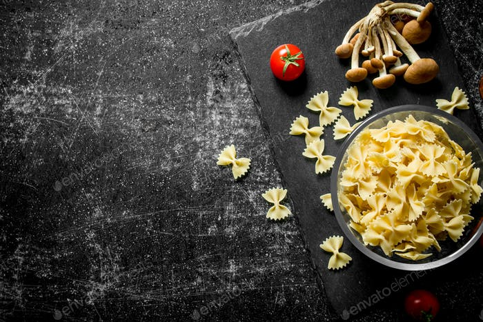 Raw Farfalle pasta in a bowl with mushrooms and tomatoes.