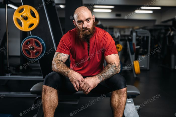 Strong athlete sitting on bench, workout in gym