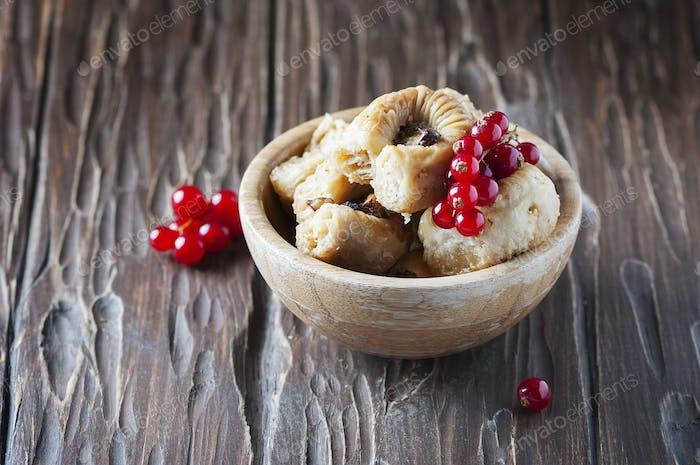 Baklava mit roten Johannisbeere auf dem Holztisch